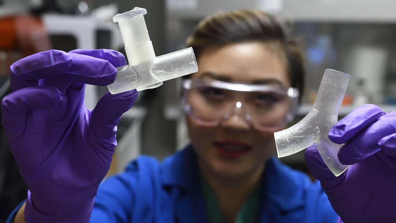 Researcher holding 3D printed ventilator splitter